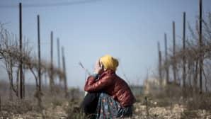 nainen istuu maassa ja itkee