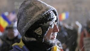 mies lumituiskussa huppu päässä