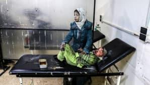 Haavoittunut lapsi makaa tutkimuspöydällä äidin pidellessä häntä.