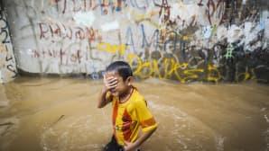 Poika kävelee tulvaveden keskellä.