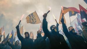 Naamioituneet miehet heiluttavat lippuja.