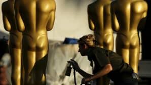 Nainen suihkumaalaa isoja Oscar patsaita.