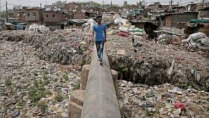 Mies kävelee jätekasan päällä Intiassa