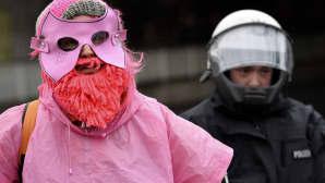 Mielenosoittaja vaaleanpunaisessa asussa ja poliisi
