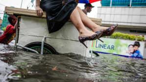 Nainen kohottaa jalkojaan, kun hän matkustaa tavarapolkupyörän päällä tulvivan kadun poikki