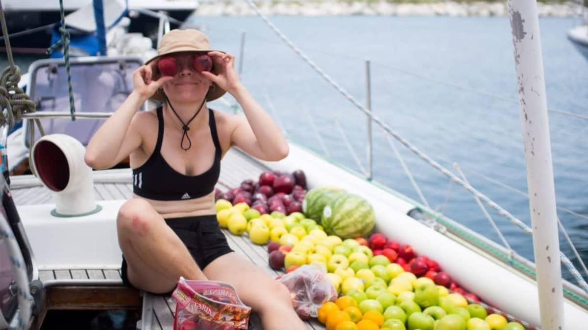Paula Ahonen istuu laivan kannella hedelmien vieressä.