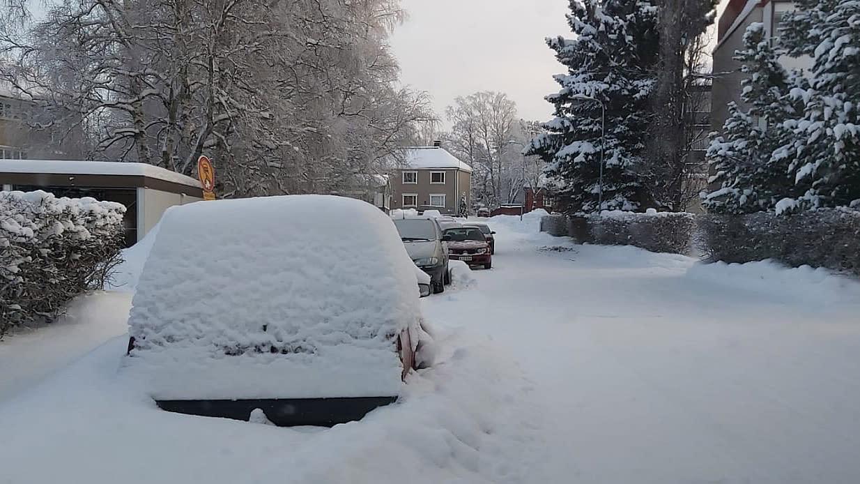 Kuvassa lumeen hautautunut auto tien varrella