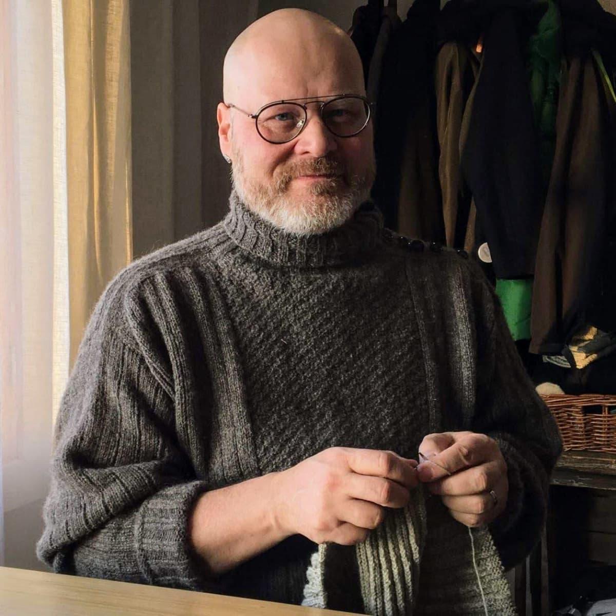 Hailuodon kunnanjohtaja Aki Heiskanen kutoo hailutolaista tikkyröijy-villapuseroa.