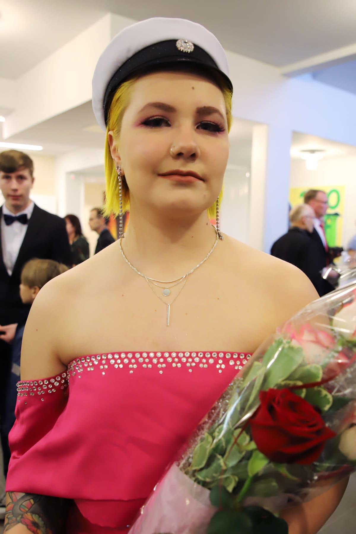 Alisa Vanhatalo valkolakin, ruusujen ja ylioppilastutkintotodistuksen kanssa.