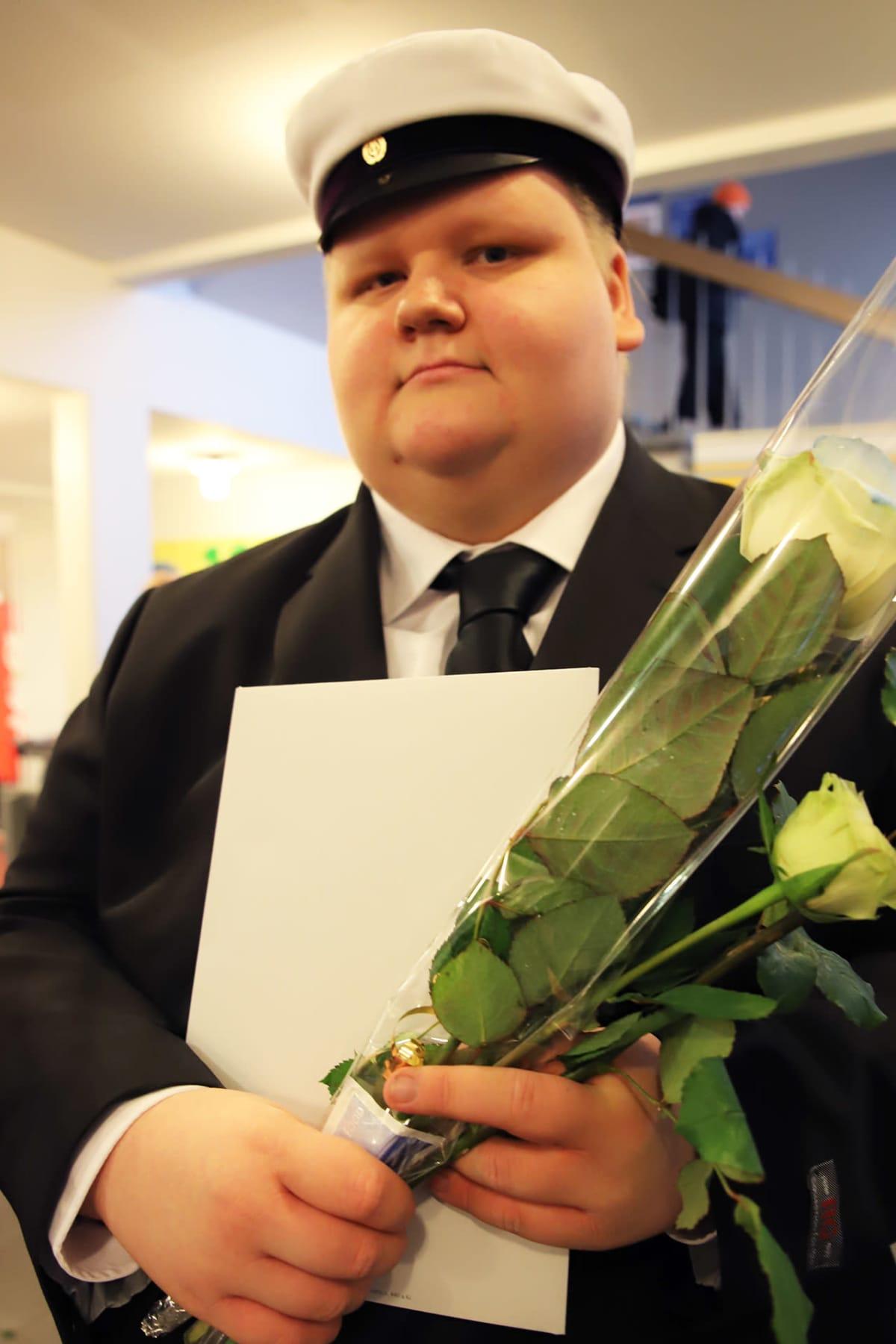 Teemu Kiviniemi valkolakki päässä, ruusut ja tutkintotodistus kädessään.