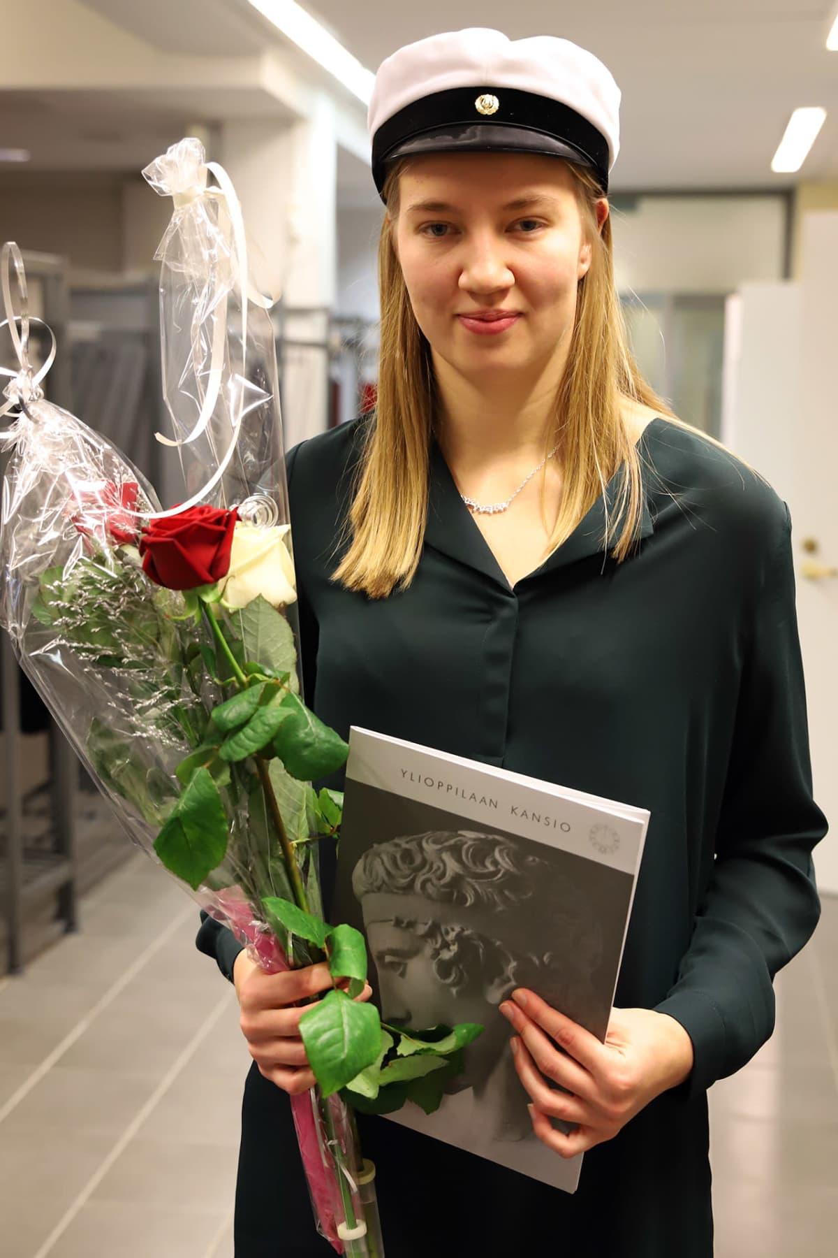 Mette Baas valkolakki päässään, kukat ja ylioppilastutkintotodistus kädessään.