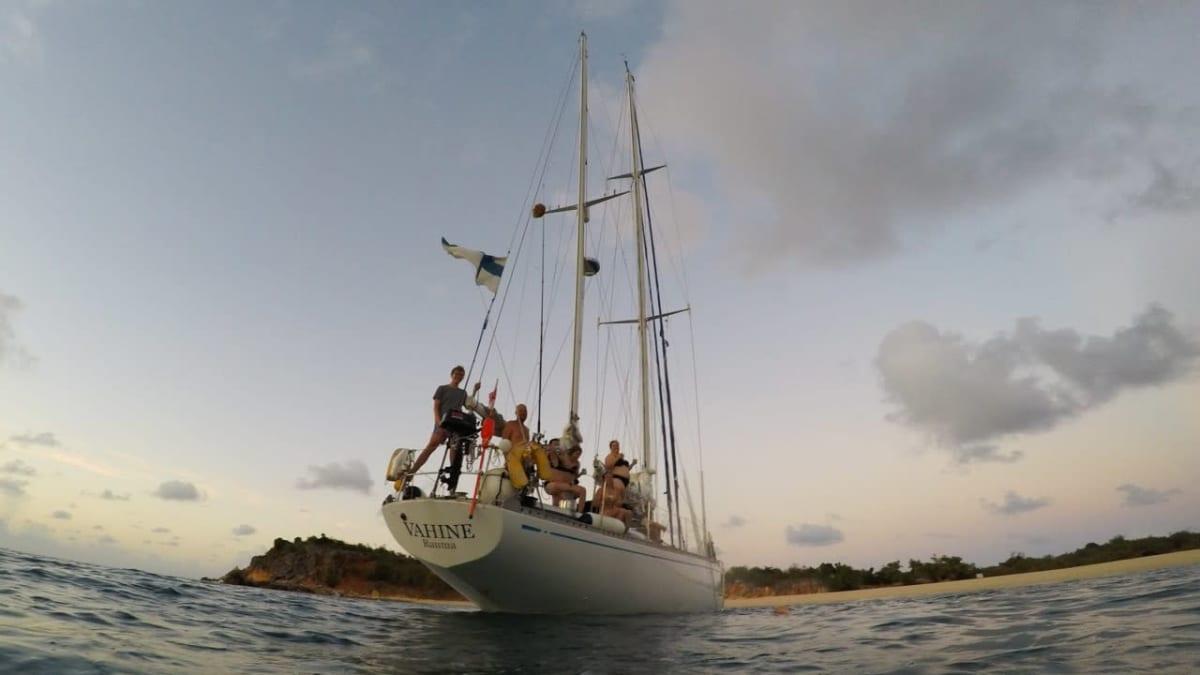 Miehistö seisoo laivan kannella auringonlaskun aikaan.