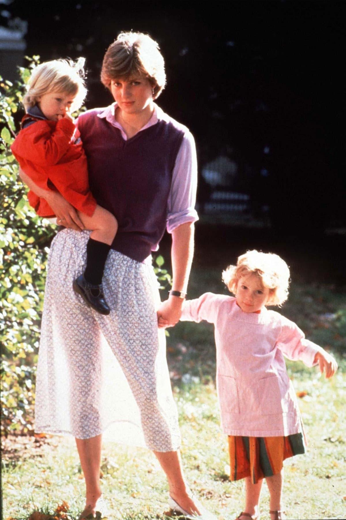 Diana yksi lapsi sylissään ja toinen vierellään. Takaa tuleva valo tekee Dianan hameesta läpinäkyvän.