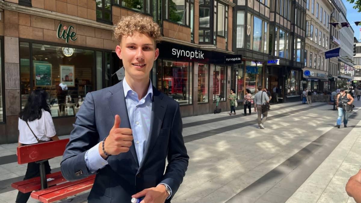 Pukuun pukeutunut nuori mies nostaa peukaloa kävelykadulla
