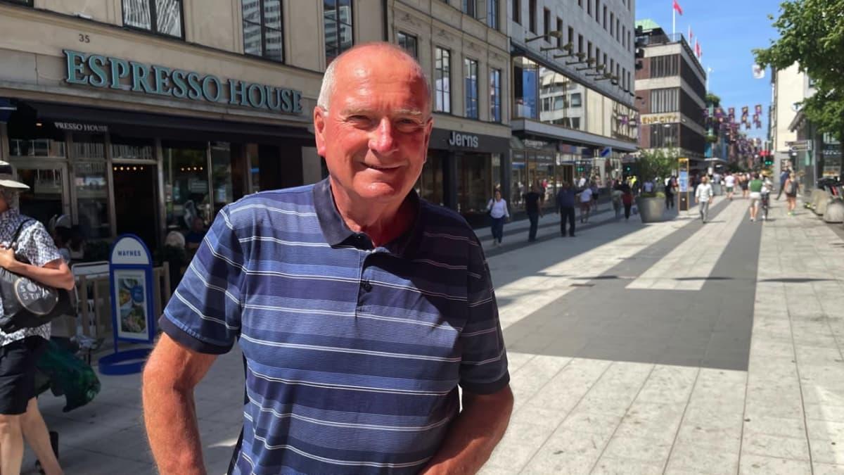 Mies sinisessä paidassa kävelykadulla