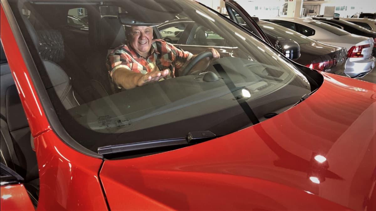 Alahärmäläinen Pentti Korpi istuu uudessa autossaan.