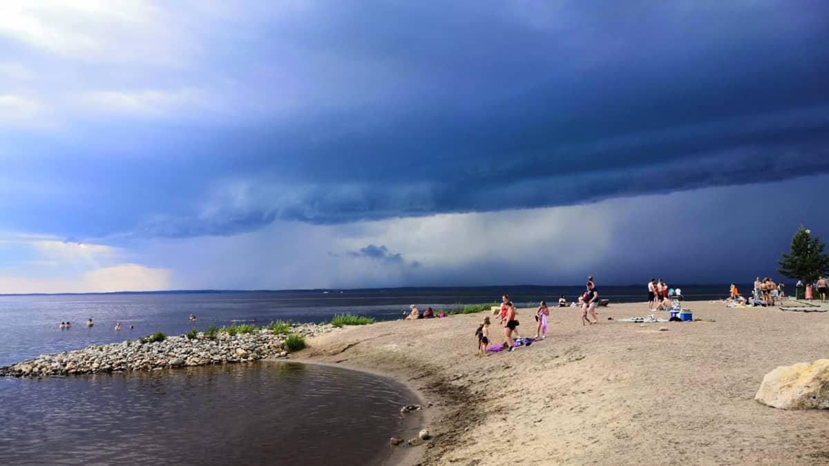 Mustat pilvet ovat järven yllä, rannalla ja vedessä on ihmisiä.