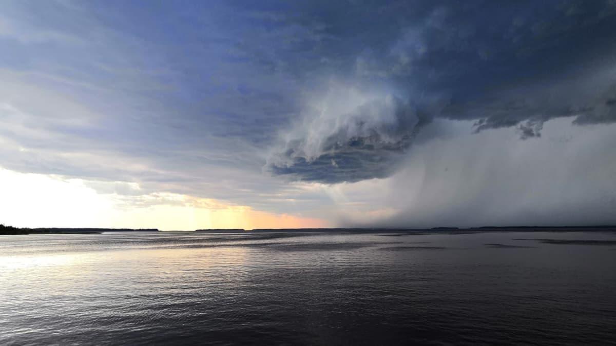 Oulujärven yllä on uhkaavan näköinen ukkospilvi, joka lähestyy mannerta. Ilta-aurinko värjää osittain järveä, vaikka pilvi peittääkin auringon.