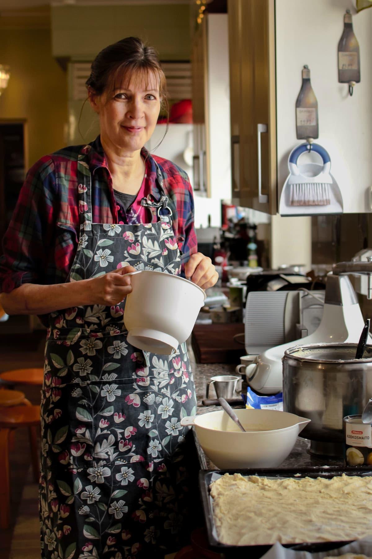 Liisa Mankinen seisoo keittiössä ruoanlaittovälineitä kädessään.