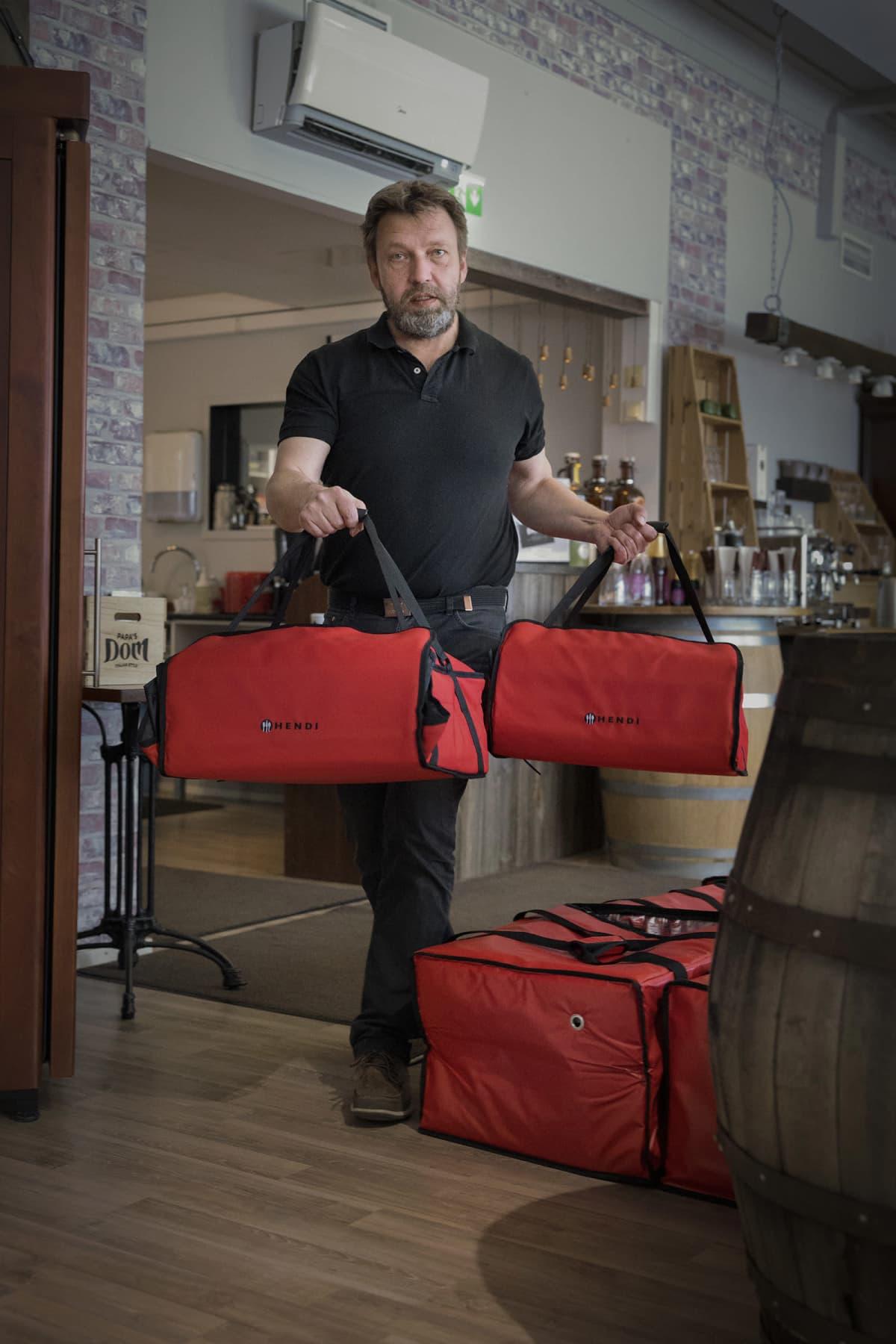 Pizzeria Domin yrittäjä Juha Parkkinen kantaa pizzalaukkuja.