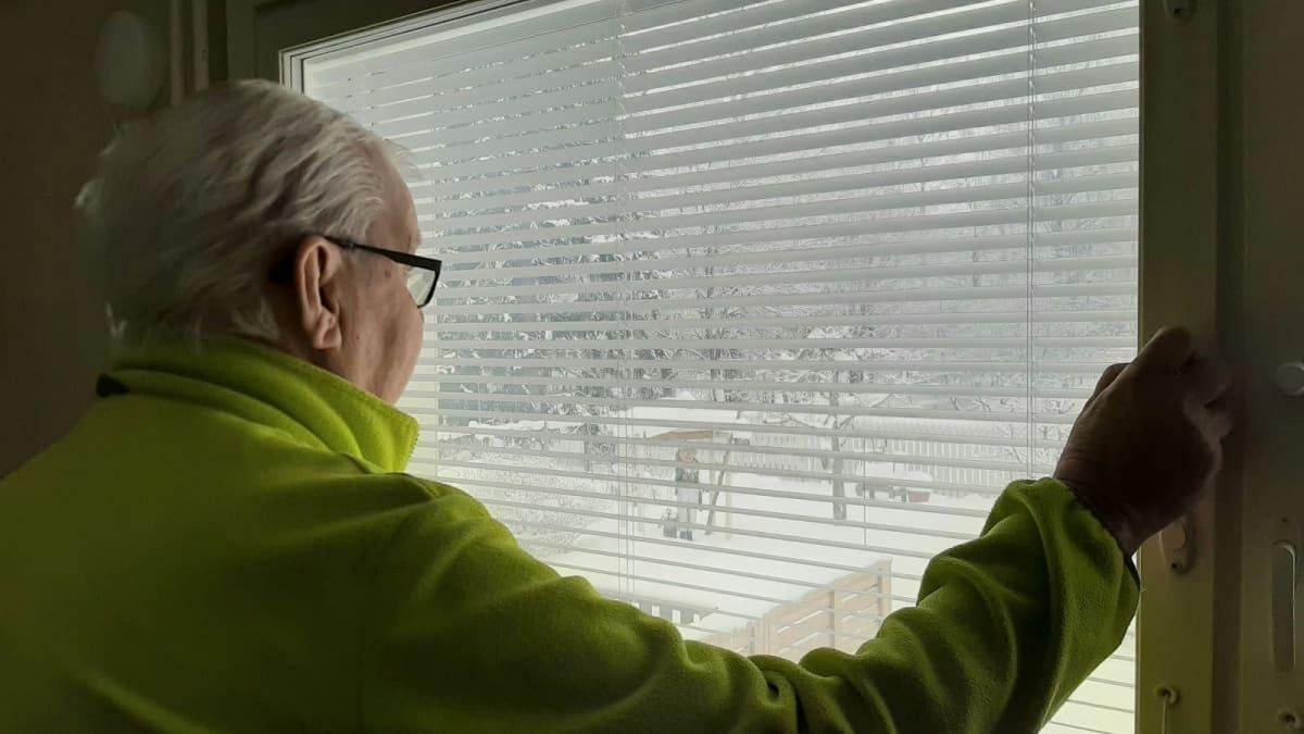 Mies katsoo ikkunasta lumimaisemaa