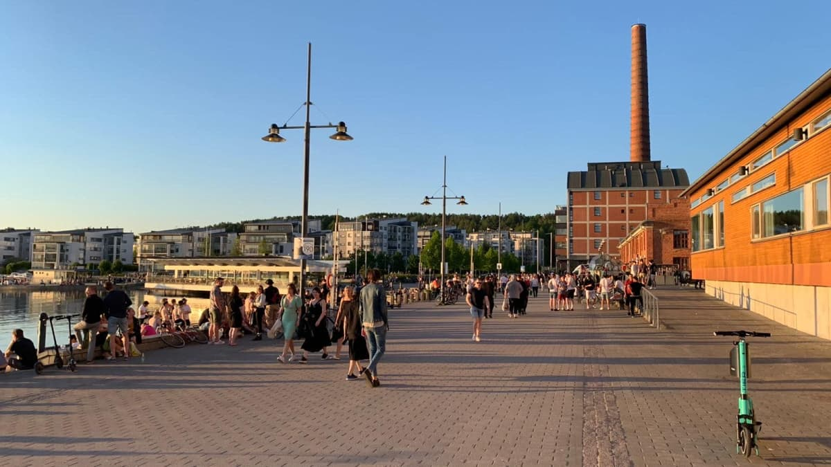 Ihmisiä kävelemässä ilta-auringossa Lahden satamassa.