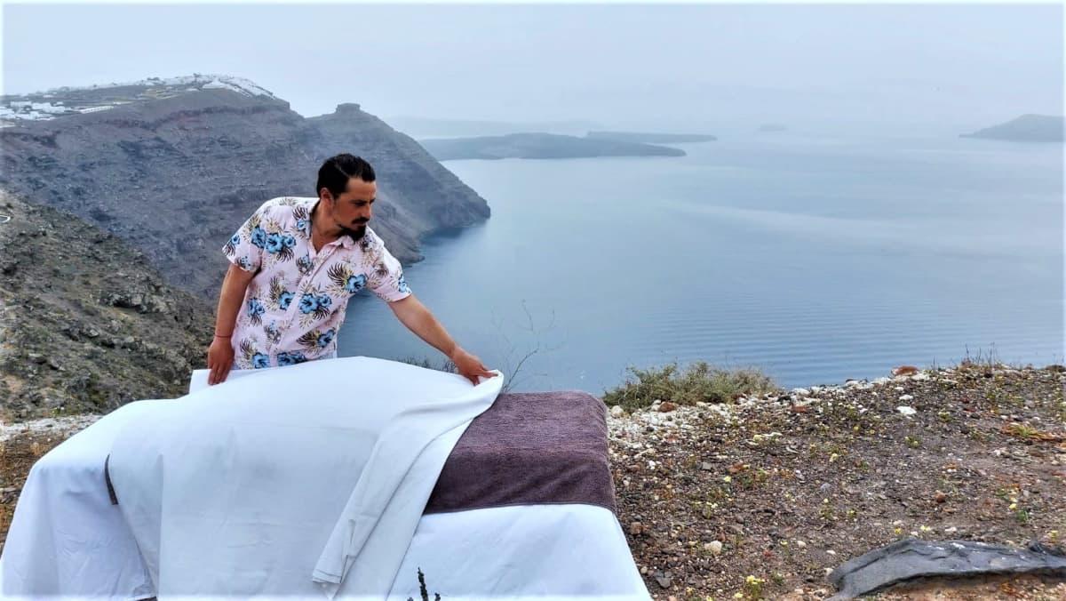 Mies levittää pyyhettä hierontapöydälle meren äärellä