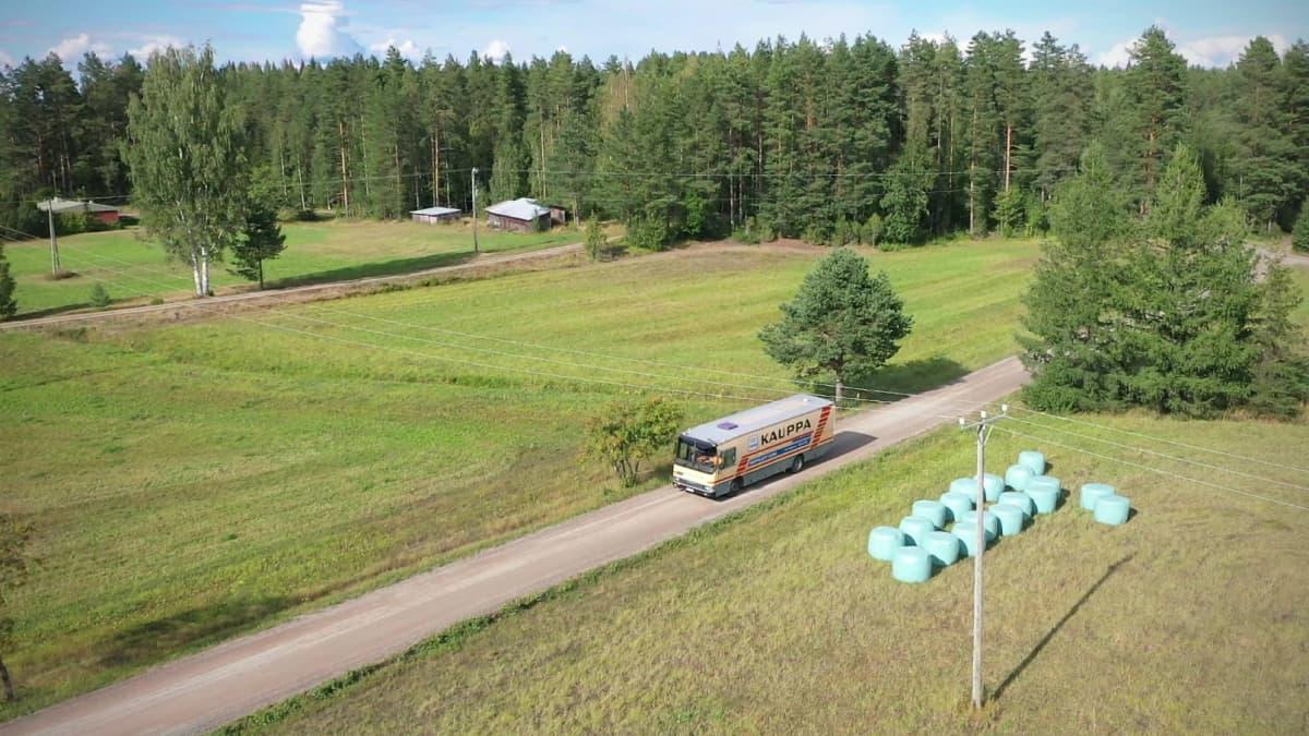 Kauppa-auto ajaa tietä peltojen keskellä aurinkoisena loppukesän päivänä.