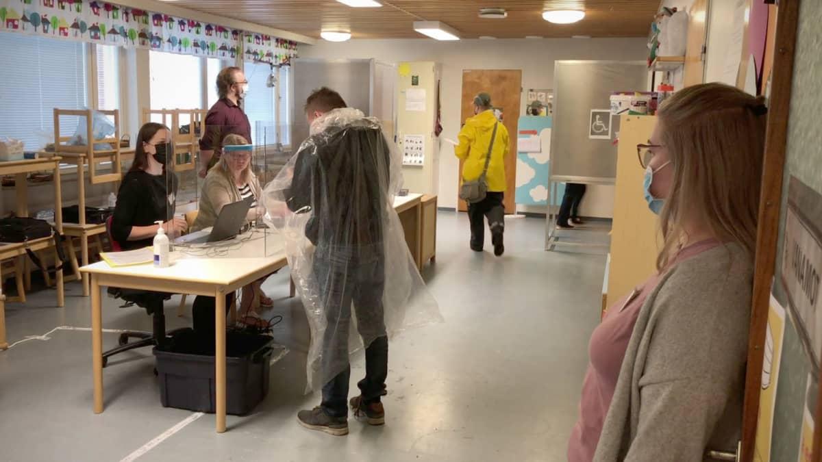 Ihmisiä sadevaatteissa äänestyspaikalla Joensuulaisessa päiväkodissa.