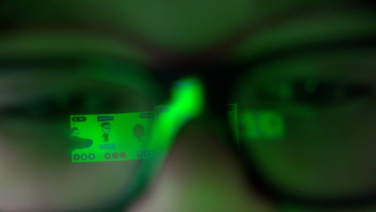 Pojan silmät ja silmälasit, joista näkyy vihreä pelimaailma.