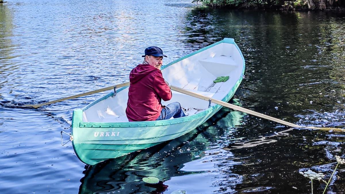 Mies soutaa venettä kohti rantaa