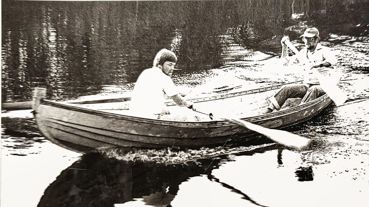 Mustavalkoisessa kuvassa kaksi henkilöä soutaa.