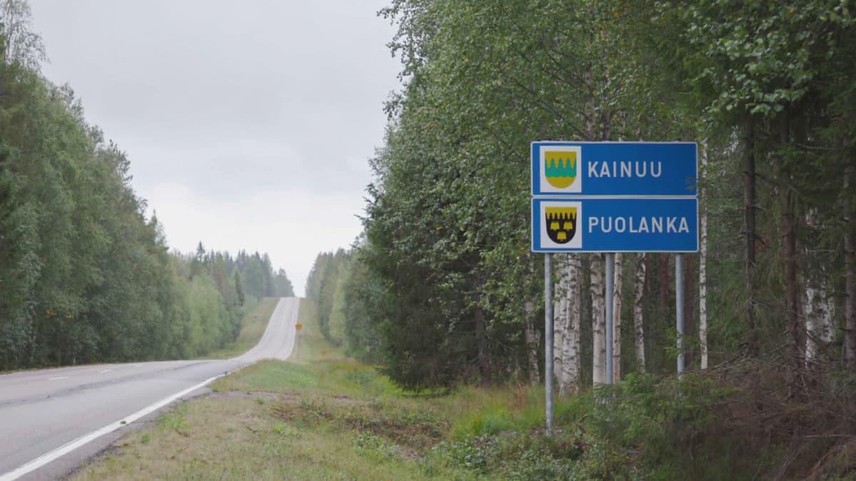 Tyhjä maantie kesällä, tien vieressä kyltti, jossa lukee 'Kainuu' ja 'Puolanka'.