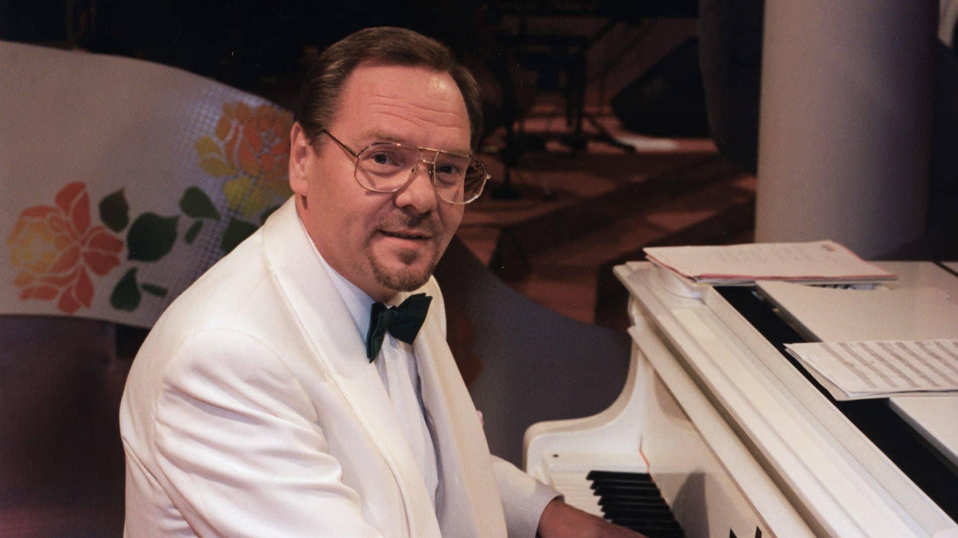 Kapellimestari Risto Hiltunen istuu pianon ääressä valkoinen smokkitakki yllään.
