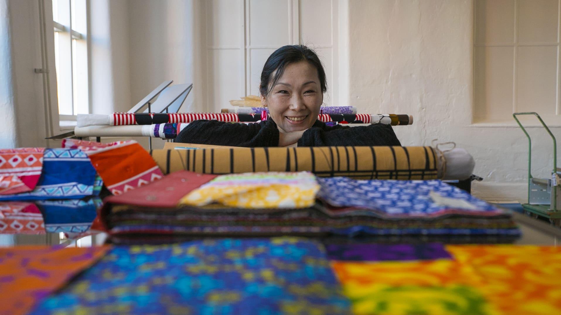 Aasilainen nainen nojaa pöytään kankaiden takana ja hymyilee .