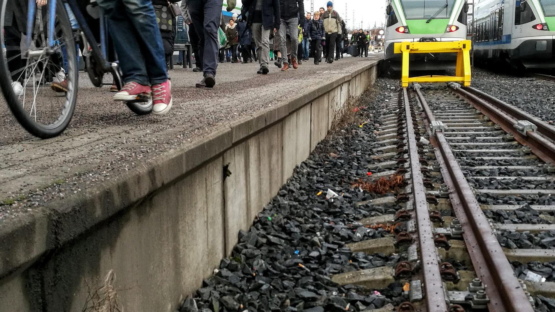 Junan raiteet Helsingin rautatieasemalla, ihmisiä kulkee ohi.