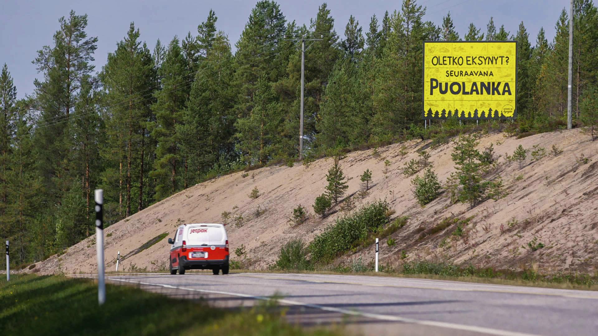 Maantie, jossa ajaa pakettiauto. Tien vieressä hiekkaisella rinteellä iso keltainen kyltti.
