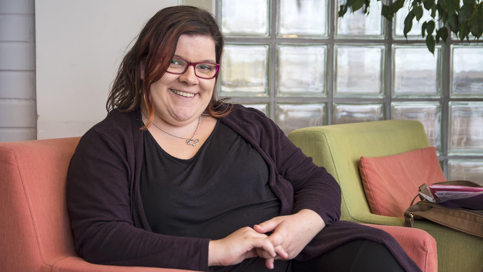 Sonja Koskela istuu  nojatuolissa ja hymyilee kameralle.