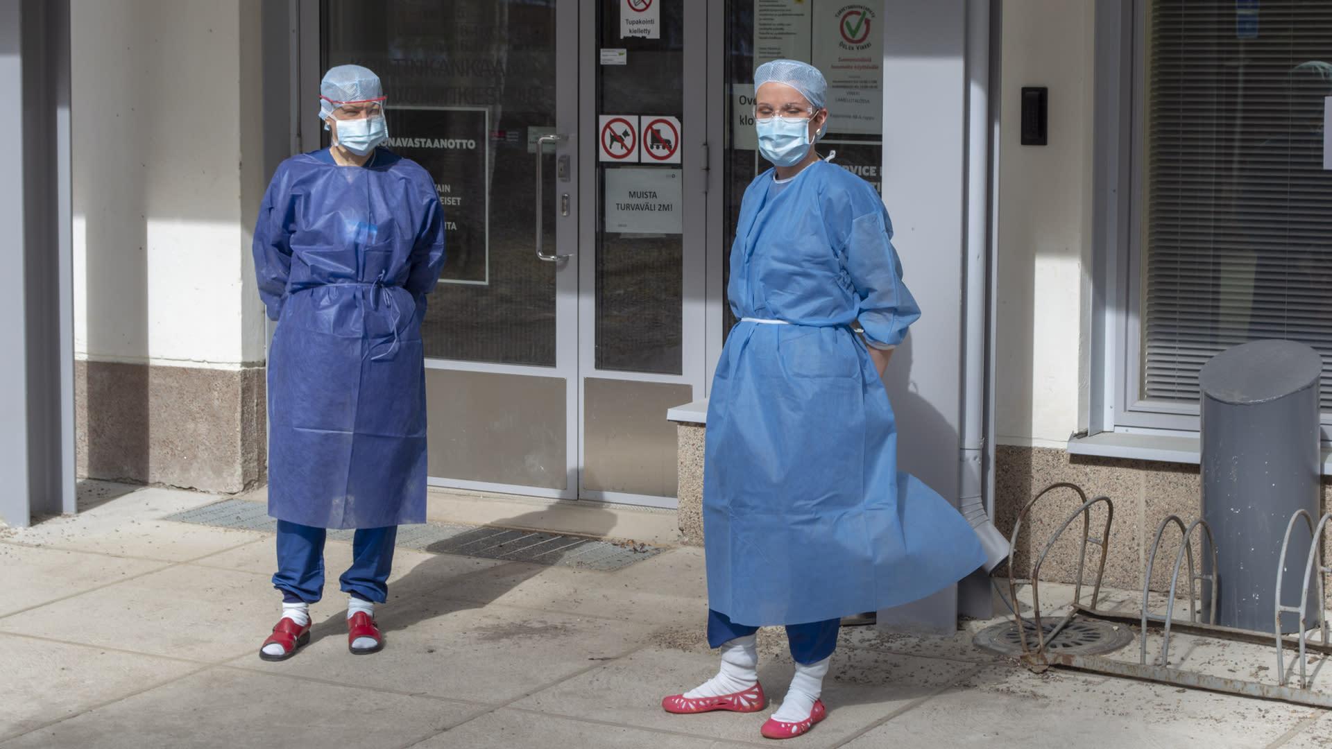 sairaanhoitajia suojavaatteissa korona vastaanotossa ulkoovella Oulussa