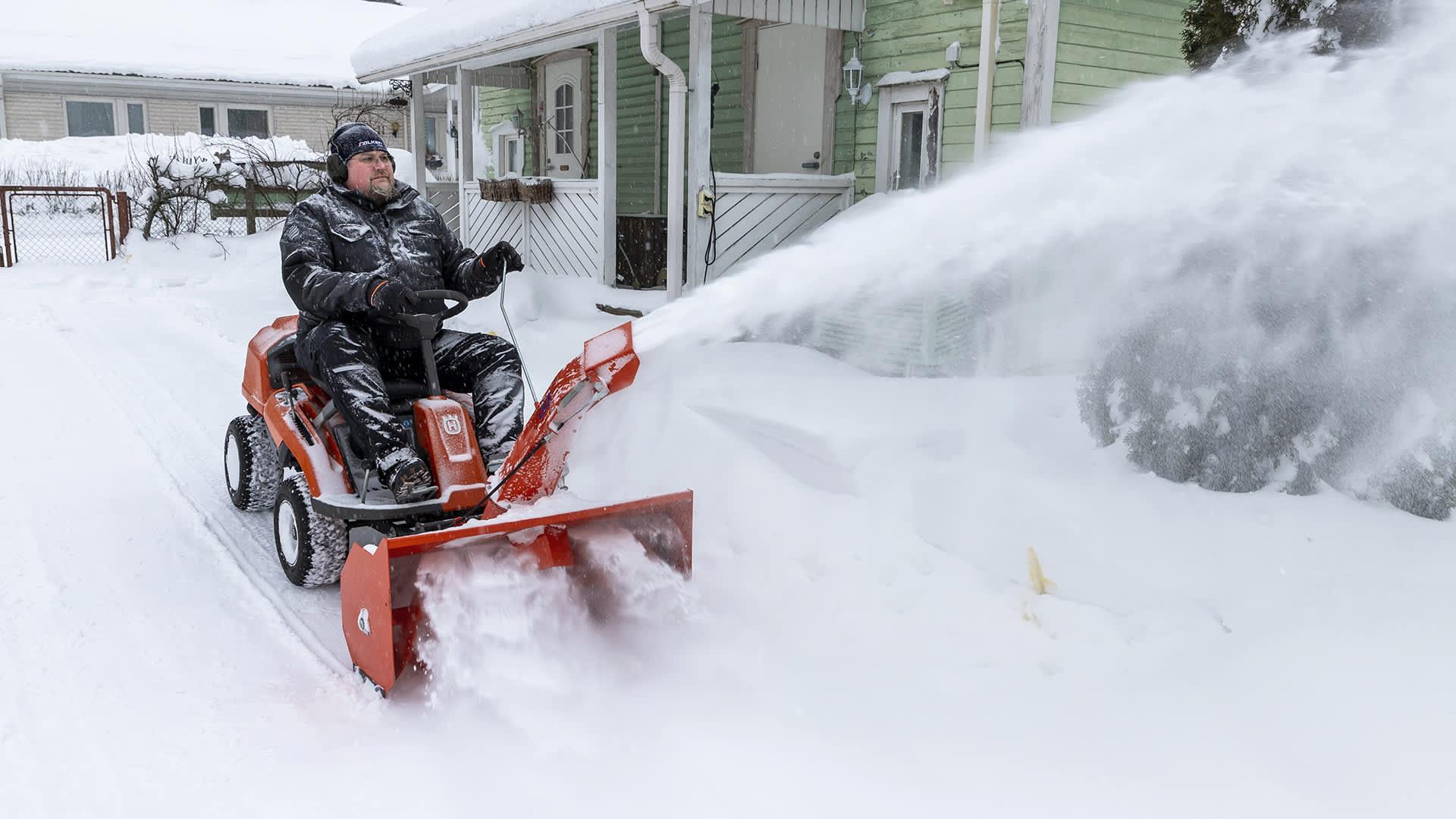 Mies ajaa lumilingolla omakotitalon pihassa. Lunta lentää torvesta.