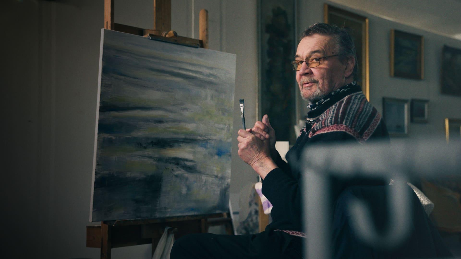 Veli Seppä katsoo kameraan hieman hymyillen pensseli kädessään edessään keskeneräinen maalaus.