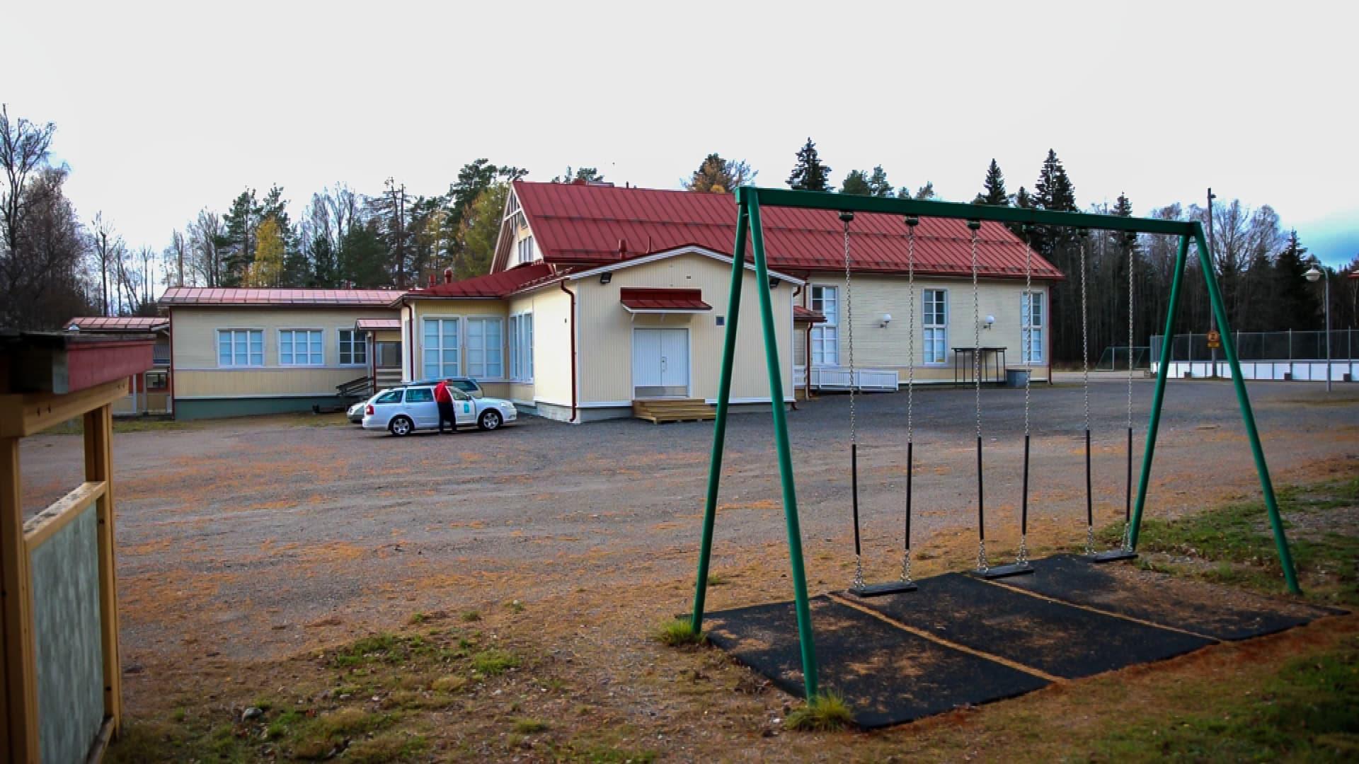 Syksyinen koulun piha. Keinut edustalla ja koulu takana.