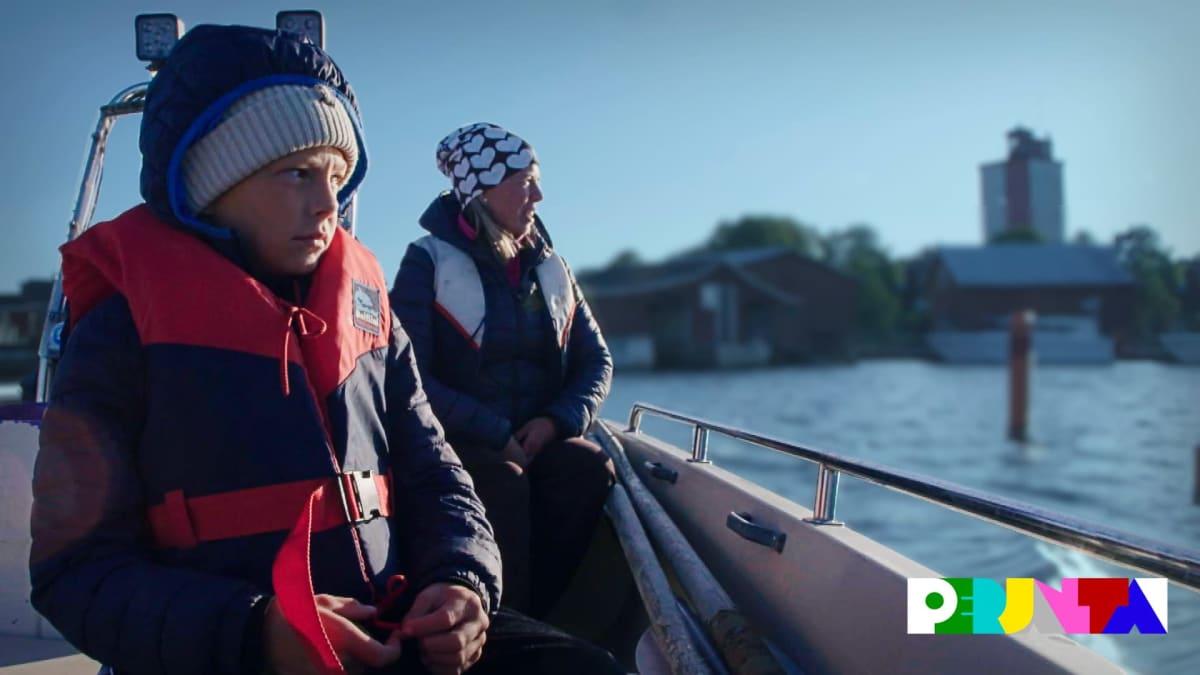 Poika ja äiti istuvat veneessä. Takana näkyy saari jolla kohoaa majakka.
