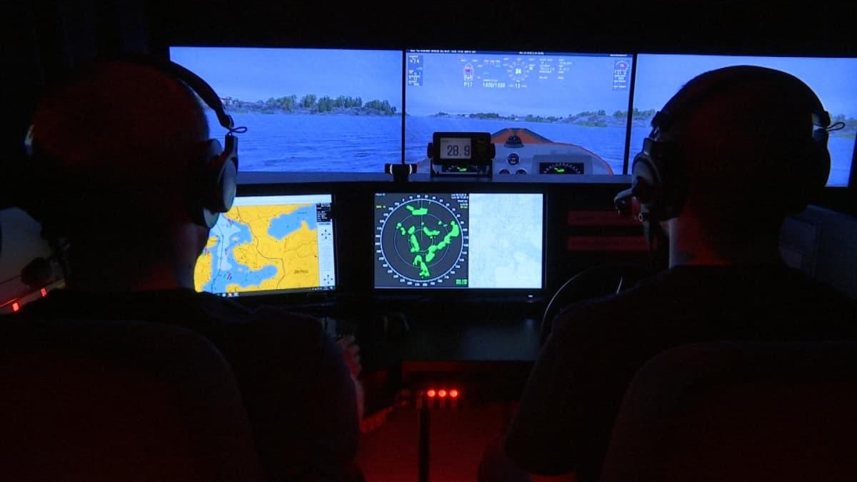 Miehet harjoittelevat ohjaamosimulaattorilla.