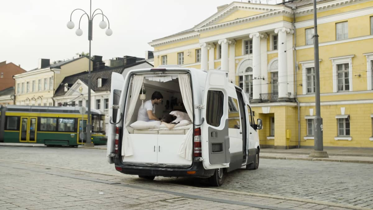 Pakettiauto on pysäköity Helsingin senaatintorille, sen takaovet ovat auki. Sisällä näkyy pariskunta, joka makoilee sängyssä.