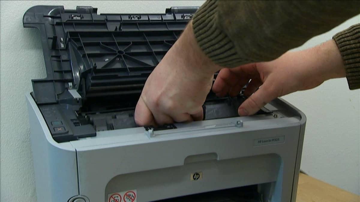 kädet tarttuvat lasertulostimen värikasettiin