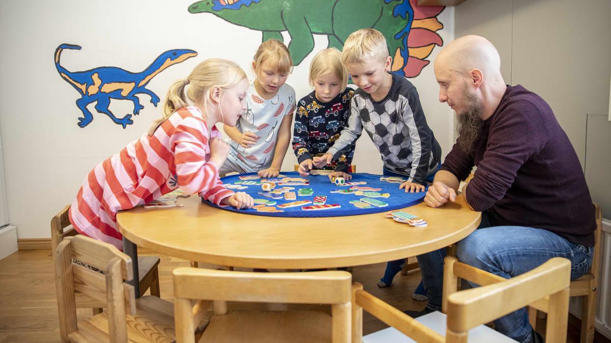 Lapset pelaa peliä lastentarhanopettajan kanssa.