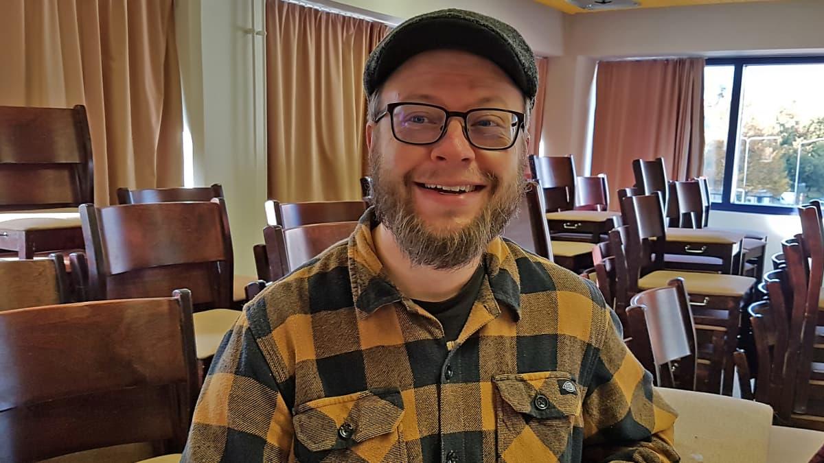 Sami Taponen seisoo huoneessa ja hymyilee
