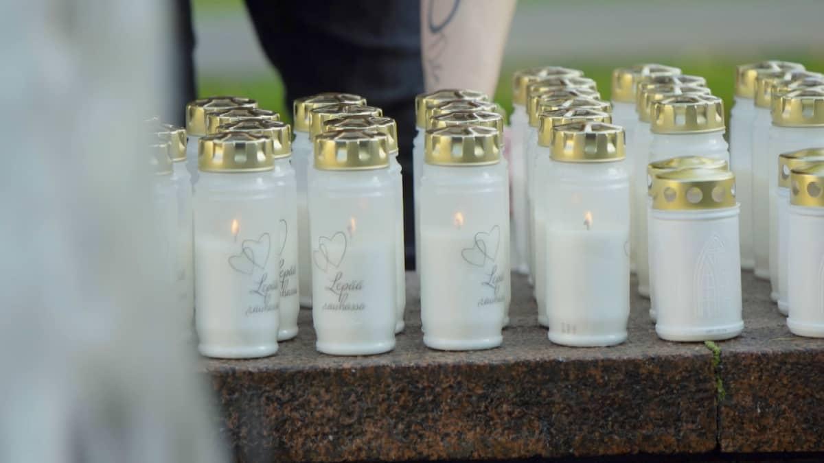 """Kynttilöitä, joissa lukee """"Lepää rauhassa""""."""