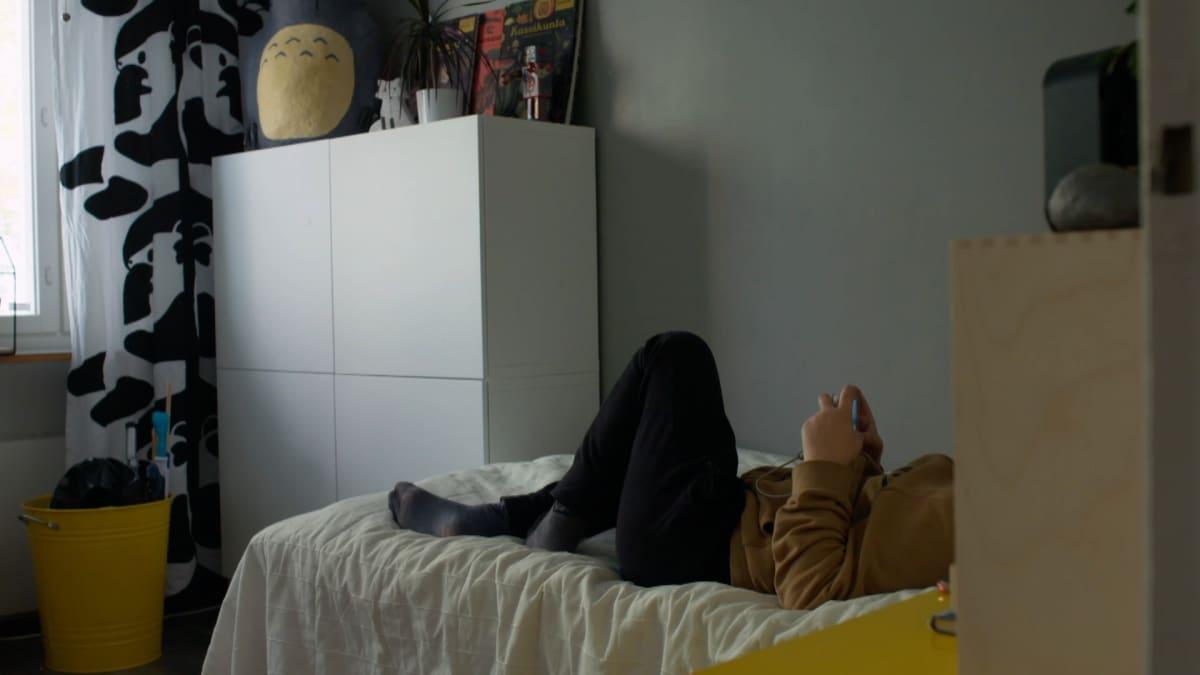 Poika makoilee sängyllä ja pelaa älypuhelimella.